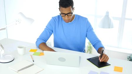 ラップトップのタブレット グラフィックとアフリカ系アメリカ人の創造的なデザイナー作業
