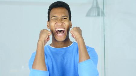 アフリカ系アメリカ人の男が彼のオフィスの成功を祝う