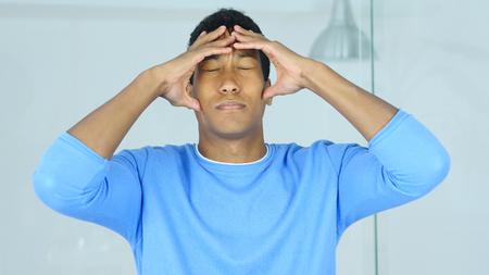 頭痛、動揺した緊張した若いアフロアメリカンの男が彼の頭を握っている
