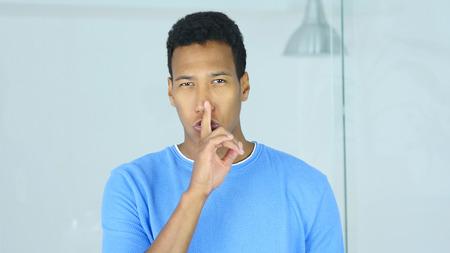 若いアフロアメリカンマンによる沈黙のジェスチャー、唇に指を 写真素材