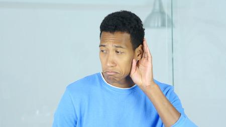 Junger afroer-amerikanisch Mann, der sorgfältig Geheimnis hört Standard-Bild - 88961464