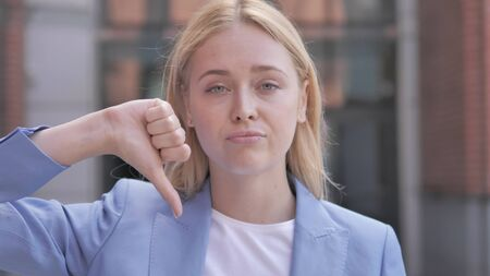 Thumbs Down by Young Businesswoman, Outdoor