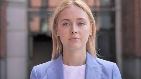 Ernsthafte junge Geschäftsfrau, die in die Kamera schaut