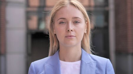 Serious Young Businesswoman Looking in Camera