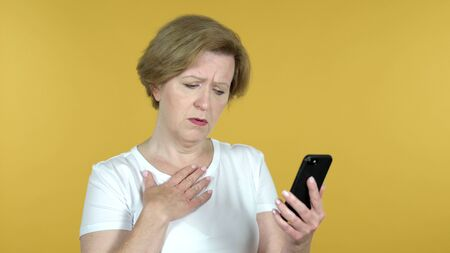 Old Woman Reacting to Loss and Using Smartphone Isolated on Yellow Background