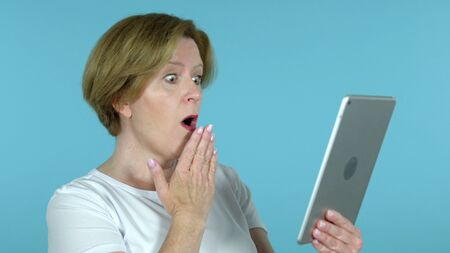 Old Woman in Shock while Using Tablet Isolated on Blue Background