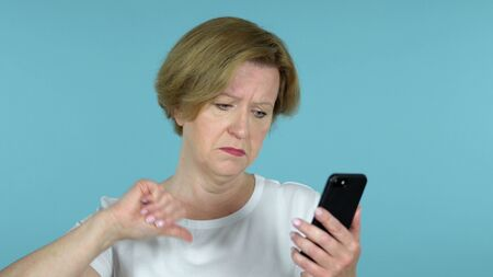 Old Woman Reacting to Loss and Using Smartphone Isolated on Blue Background