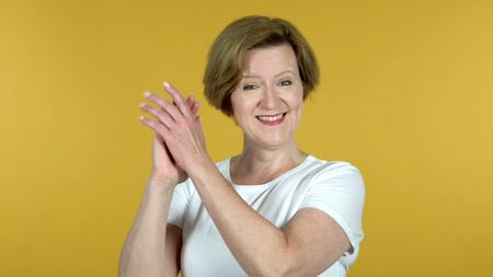 Clapping Old Woman, Applauding Isolated on Yellow Background 版權商用圖片