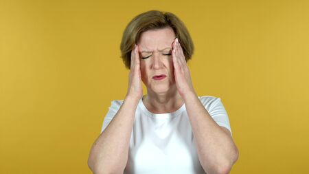 Old Woman with Headache Isolated on Yellow Background 免版税图像