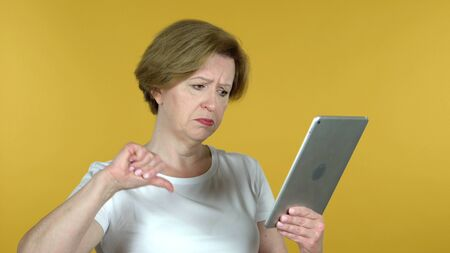 Old Woman Reacting to Loss on Tablet Isolated on Yellow Background 版權商用圖片