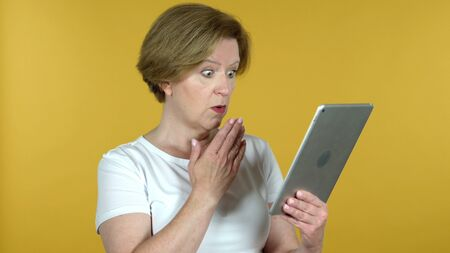 Old Woman in Shock while Using Tablet Isolated on Yellow Background