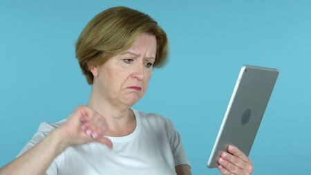 Old Woman Reacting to Loss on Tablet Isolated on Blue Background 版權商用圖片