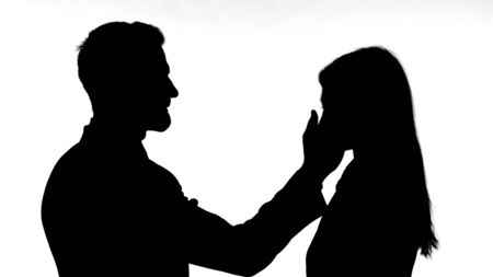 The Silhouette of Man Slapping Woman Against White Background