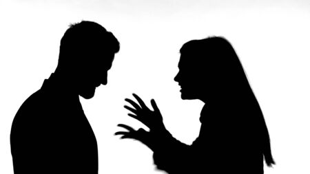 The Silhouette of Woman Fighting with Man against White Background 免版税图像