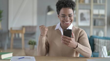 The cheerful African Girl Using Her Smart phone