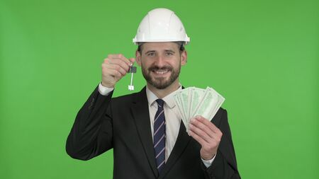 The Cheerful Engineer with House key and Money against Chroma Key