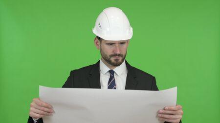The Ambitious Engineer Reading Construction Blueprint against Chroma Key Zdjęcie Seryjne