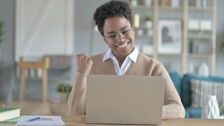 The cheerful Young African Girl working on laptop
