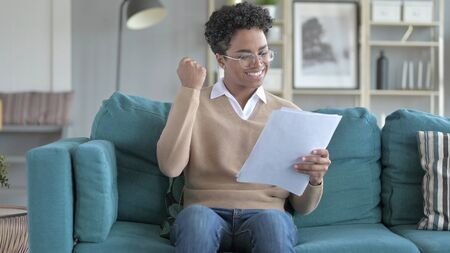 The Happy Young African Girl Excited while Reading Contract