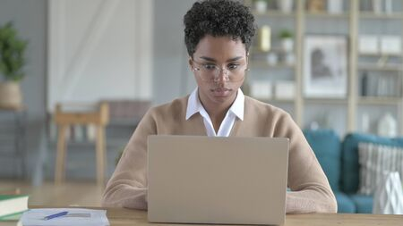 The Working African Girl Using Her laptop on Her Table