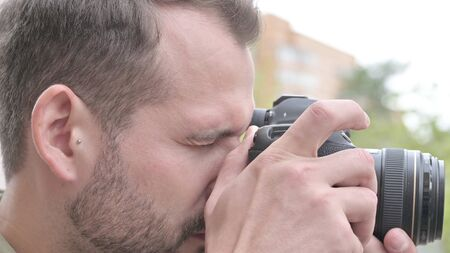 The Close Up of Young Man Taking Photographs on Camera