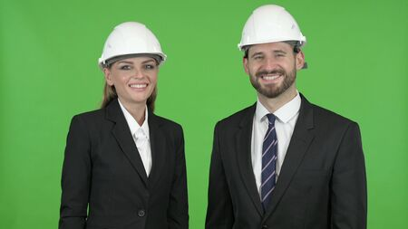 The Two Construction Engineers Smiling While Looking at the Camera Against Chroma Key