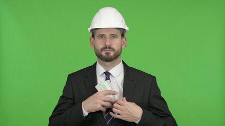 The Young Engineer putting Money in Pocket against Chroma Key Zdjęcie Seryjne