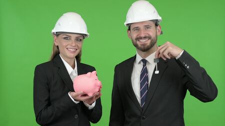 The Engineers Posing with Piggy Bank and Construction Equipment Against Chroma Key