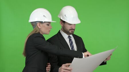 The Male and Female Engineers Studying Blueprint Against Chroma Key