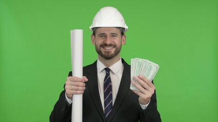 The Cheerful Engineer with Blueprint and Money against Chroma Key