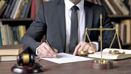 Primo piano del documento della firma della mano del giudice nell'aula del tribunale Archivio Fotografico