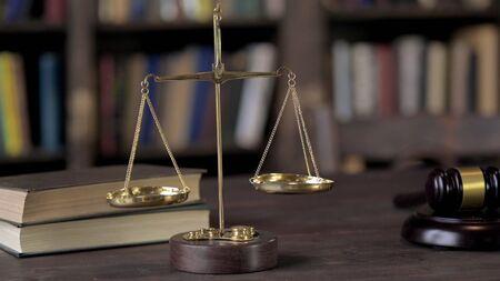 Escala de equilibrio de latón dorado sobre mesa de madera de juez