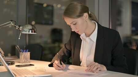 The Ambitious Businesswoman doing Writing Documents at Night Stock fotó
