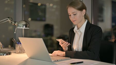 The Young Businesswoman using Smartphone on Office Desk at Night