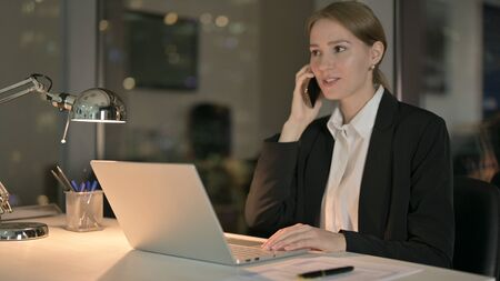 The Cheerful Businesswoman Talking on Smartphone in Office at Night