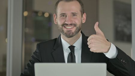 The Close Up of Handsome Businessman showing Thumbs Up at Night