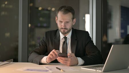 The Serious Businessman using Smartphone in Office at Night Stock fotó