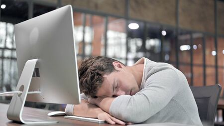 Tired Young Guy having Quick Nap at Office Desk