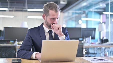 Młody biznesmen kaszle podczas pracy na laptopie