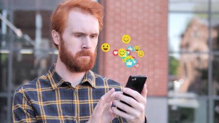 Redhead Beard Man Using Smartphone, Flying Emojis, Smileys and Likes