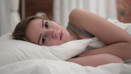 Close Up of Young Woman Looking at Camera in Bed