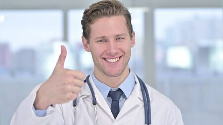 Portrait of Young Male Doctor showing Thumbs Up in Office Stock fotó