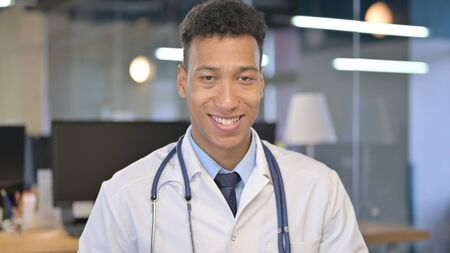 Portrait of Smiling Young Doctor Looking at Camera