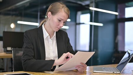Young Businesswoman Reading Documents in Office Stock fotó