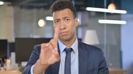 Portrait of Young Businessman saying No with Finger Sign
