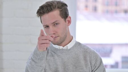 Portrait of Creative Young Man Pointing Finger at Camera