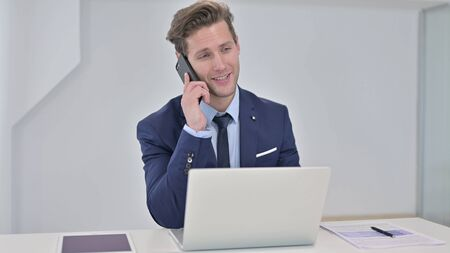 Serious Young Businessman Working on Laptop and Talking on Smartphone