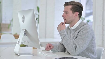 Creative Young Man Thinking and Working on Desktop