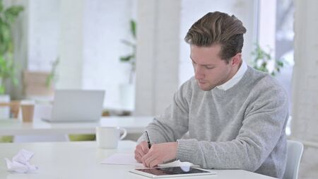 Young Man Writing on Paper at Work