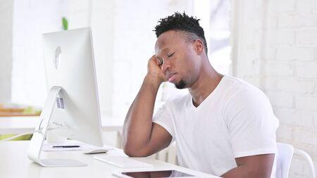 Sleepy Young African Man Sleeping in Office Imagens